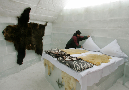 A woman arranges the bed in a room at the Balea Lac Ice Hotel in Romania.