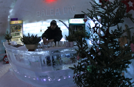 A bartender arranges ice glasses inside the Balea Lac Hotel of Ice in the Fagaras mountains.