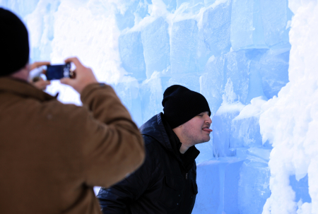 A tourist licks the outside wall of the Balea Lac Hotel of Ice in the Fagaras mountains.