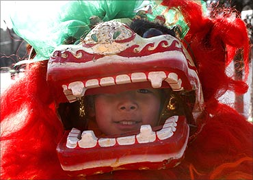 A child looks at the camera as he practises lion dance at a park in Beijing.