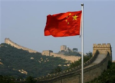A Chinese flag flies in front of the Great Wall of China, located north of Beijing.