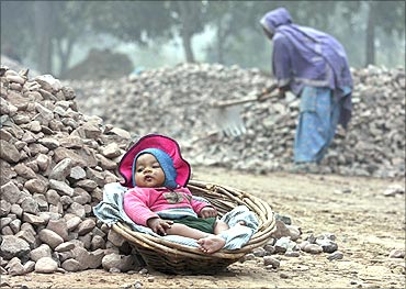 Five-month-old Roshni, child of a woman labourer (R), rests in a basket at a roadside construction,