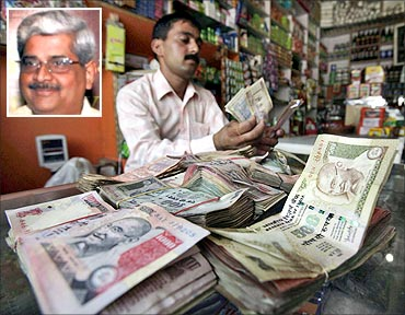 A shopkeeper counts notes inside his shop in Jammu. (Inset) R Gopalan.