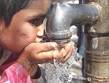 A flood victim drinks water from a hand pump in Murad Chandio village.
