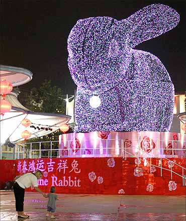 A mother, daughter stand in front of a four-storey-high topiary rabbit at Resorts World Sentosa.