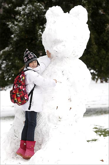 A young girl touches a snowman in Green Park, in central London.