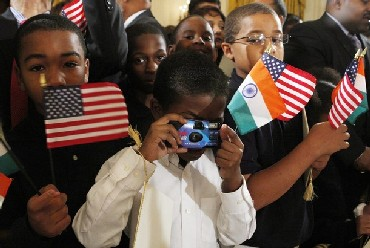 Guests hold the flags of the United States and India as U.S. President Barack Obama welcomes Indian Prime Minister Manmohan Singh.