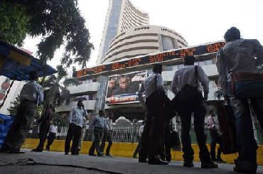People look at a large screen on the facade of the Bombay Stock Exchange (BSE) building in Mumbai
