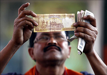 A worker at a fuel station checks a 500 Indian rupee note after filing a vehicle with fuel.