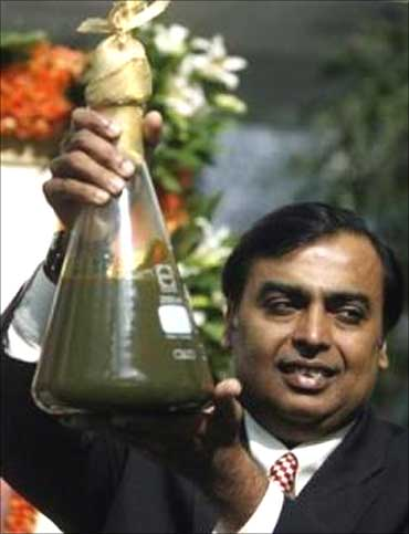 Mukesh Ambani, Chairman of Reliance Industries, holds a jar containing the first crude oil produced from the company's KG-D6 block.