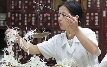 A Chinese pharmacist fills a prescription of Chinese herbal medicine at a herbal medicine store.