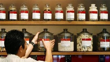 A shop assistant arranges jars containing roots and herbs at a Chinese medicine shop.