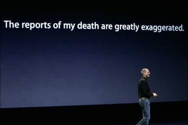 Steve Jobs stands beneath a sign that makes light of reports on his health at an Apple event.