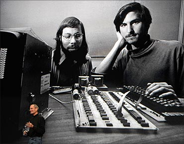Steve Jobs stands under a photo of him and Apple-co founder Steve Wozniak, January 27, 2010.
