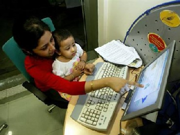 Customers at a high-speed broadband internet cafe by run by Reliance Infocomm.