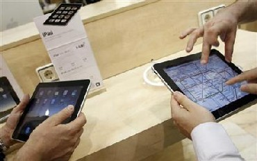 Visitors check out Apple iPads at an Apple retail store.