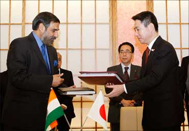 Trade Minister Anand Sharma and Japan's Foreign Minister Seiji Maehara exchange documents after signing the Comprehensive Economic Partnership Agreement in Tokyo on February 16, 2011.