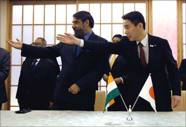 Trade Minister Anand Sharma (L) and Japan's Foreign Minister Seiji Maehara gesture after signing the Comprehensive Economic Partnership Agreement (CEPA) in Tokyo February 16, 2011.