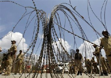 Policemen stand guard behind concertina wire barricade set up to stop Kashmiri protesters during a curfew in Srinagar.