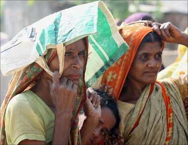 Women queue in the summer heat to collect rice from a discount shop run by the government.