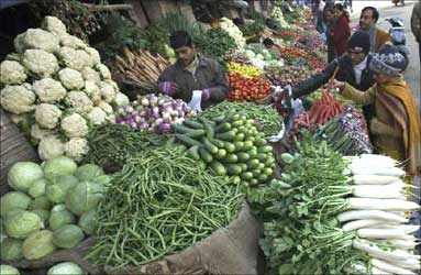 People buy vegetables at a market in Jammu.