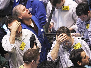 Traders work in the oil options pit on the floor of the New York Mercantile Exchange in New York City. World stocks fell as a growing revolt in Libya drove oil prices to 30-month highs.