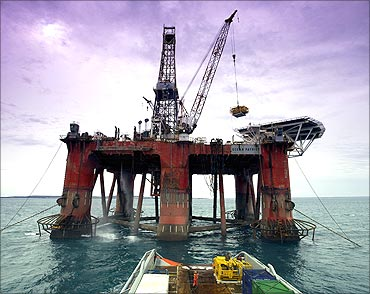 A worker is seen on a boat as it approaches an oil rig.