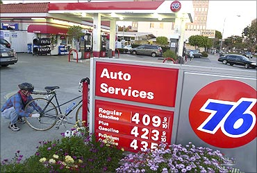 Eric Eastman fixes the wheel on his bicycle next to a board displaying gas prices at a petrol station in Los Angeles.
