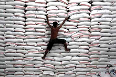 A worker climbs on a pile of rice stock inside a warehouse in Bicutan, south of Manila, the Philippines.