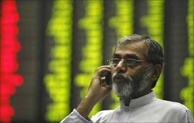 A man talks on a mobile phone near an electronic board displaying stock prices at the Karachi Stock Exchange.