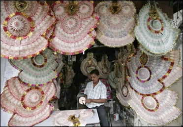 A shopkeeper staples Indian currency notes to make garlands at a market.
