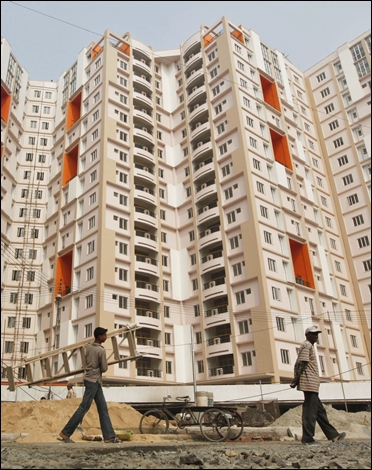 Labourers walk past a residential estate under construction in Kolkata.