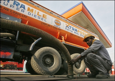 An employee refills petrol from a tanker at a fuel station at Noida.