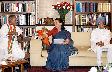 Sonia Gandhi speaks with Pranab Mukherjee as India's PM Singh watches in New Delhi.