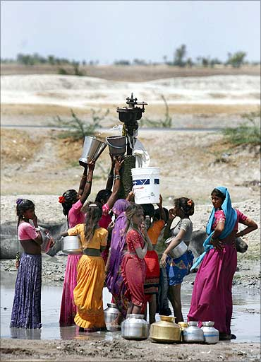 Women fill buckets with drinking water that is leaking from a broken pipeline at Dharji village.