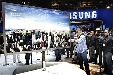 A reporter touches a 75-inch, full HD 3D LED television by Samsung Electronics.