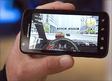 A demonstrator plays a racing game on an Android-based Motorola Atrix smartphone.