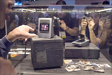 People look at Polaroid G30 cameras after the they were introduced by singer Lady Gaga.