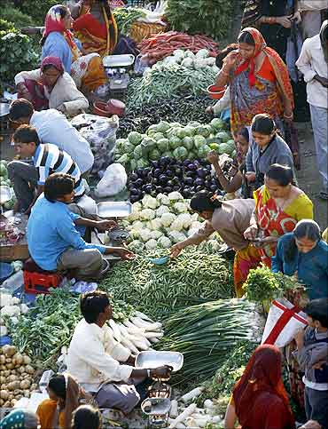 People shop at an open air vegetable and fruit market in Ahmedabad.