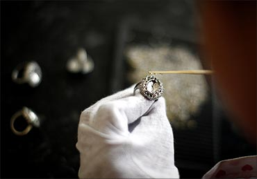 An employee sets stones on a replica of the British royal engagement ring at a jewellery factory.