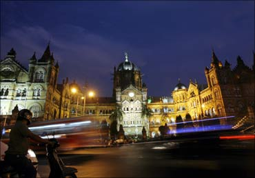 A scooterist stops in front of Chhatrapati Shivaji Terminus railway station.