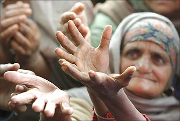 An old lady raises her hands to receive food from a roadside charitable community kitchen.