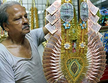 Dhanender Kumar Jain, 65, a shopkeeper, holds a garland made of Indian currency.