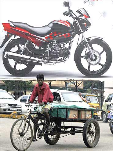 A vendor cycles past a billboard advertisement of a motorcycle in Chennai.