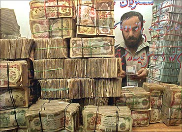 An Afghan money changer counts money at his shop in Kabul.