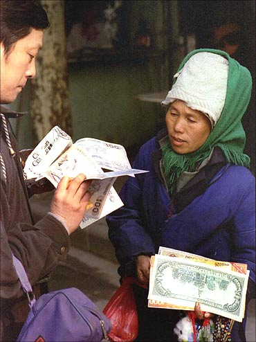 A Chinese woman sells enlarged copies of various currency notes.