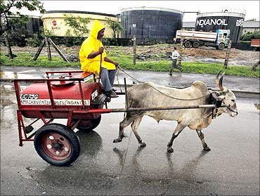 A worker transporting kerosene in a bullock cart travels past Indian Oil Corporation's fuel depot in Mumbai.