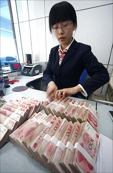 An employee counts Yuan banknotes at the Suining City Commercial Bank in Suining.