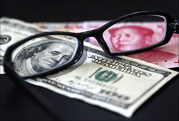 A US dollar note (L) and a Chinese Yuan banknote are seen through a pair of spectacles.