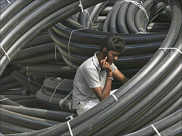 A construction supervisor speaks on a mobile phone amid rolls of underground telephone cable pipes.